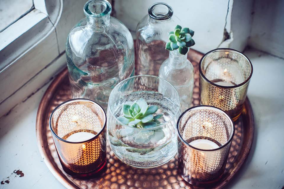Deko-Inseln schaffen Wohlfühlatmosphäre. So können zum Beispiel verschiedene Kerzengläser mit Blumenvasen kombiniert werden.
